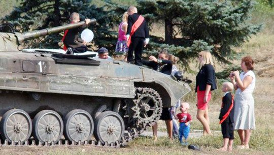 "Pic shows: Kid arriving  in thank at school in the first day. The first day at school proved particularly unforgettable for one Ukrainian lad after his dad took him there in a tank. The unnamed little boy had apparently been nervous about turning up for his first day at a new school in the city of Donetsk in south-eastern Ukraine. But all nerves vanished after his dad drove him there in style on a tank, in a stunt that instantly made him popular with all his new school friends. Pictures of kids clambering over the tank, rushing up to touch it and chatting to the tank commander, the boy's dad, were widely circulated and proved it was extremely popular. The dad is a soldier in the Ukraine and most likely one of the Russian-backed separatists who are carrying out the defence of Donetsk, a city which has seen frequent fighting despite a supposed ceasefire being in place. Parent Vitaly Dolgorukova said: ""It's not unusual to see tanks around here but I've never seen one doing the school run before, I thought it was a really fun idea that took away the nerves of a lot of the new kids."" (ends)"