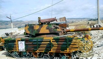 T-55 protected by slat armor and poster of Assad