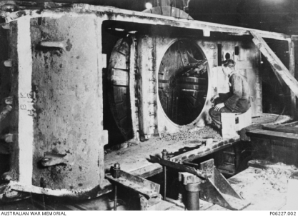A metal worker watches carefully, as the enormous chuck and cutting tool on a Scott Lathe, machines out the turret ring on the cast hull of an Australian Cruiser (AC) tank at Hadfields Australia Ltd