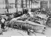 Australian metal workers at the foundry company, Bradford Kendall Ltd, (Government Annexe 89), working in the fettling and dressing bay on recently cast hulls of Australian Cruiser (AC) tanks.
