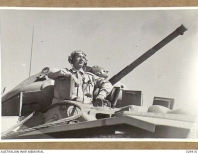 PUCKAPUNYAL, AUSTRALIA. 1943-03-01. THE DRIVER OF AN ALL-AUSTRALIAN CRUISER TANK STANDING UP IN HIS COCKPIT.